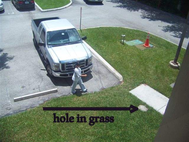 Hole in grass covered with sand next to sidewalk.