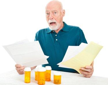 Man Stressed Holding Bills. Nex to Prescription bottles.